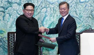 FILE - In this April 27, 2018 file photo, North Korean leader Kim Jong Un, left, and South Korean President Moon Jae-in shake hands after signing on a joint statement at the border village of Panmunjom in the Demilitarized Zone, South Korea. The two Koreas will hold a high-level meeting on Wednesday, May 16, 2018, to discuss setting up military and Red Cross talks aimed at reducing border tension and restarting reunions between families separated by the Korean War. (Korea Summit Press Pool via AP, File)