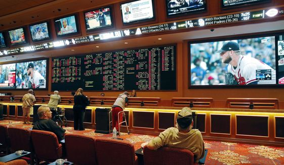 In this Monday, May 14, 2018 photo, people make bets in the sports book at the South Point hotel and casino in Las Vegas. Now that the U.S. Supreme Court has cleared the way for states to legalize sports betting, the race is on to see who will referee the multi-billion-dollar business expected to emerge from the decision.  (AP Photo/John Locher) **FILE**