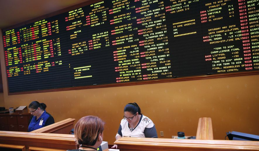 Crystal Kalahiki, right, takes a bet in the sports book at the South Point hotel-casino, Monday, May 14, 2018, in Las Vegas. The Supreme Court on Monday gave its go-ahead for states to allow gambling on sports across the nation, striking down a federal law that barred betting on football, basketball, baseball and other sports in most states. (AP Photo/John Locher)