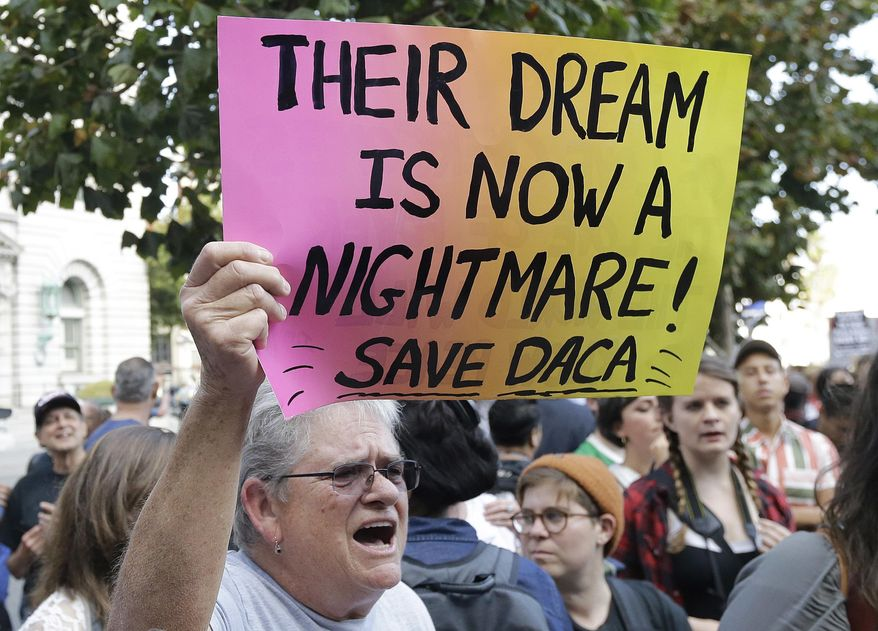 In this Sept. 15, 2017, file photo, Judy Weatherly, a supporter of the Deferred Action for Childhood Arrivals (DACA) holds up a sign during a protest outside of the Federal Building in San Francisco. (AP Photo/Jeff Chiu, File)