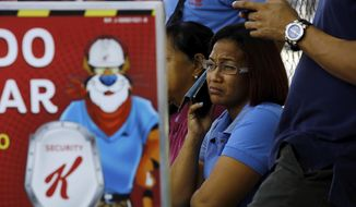 Workers wait for information about their jobs outside the Kellogg's factory in Maracay, Venezuela, Tuesday, May 15, 2018. Workers arriving Tuesday for the early shift were surprised to find a notice taped to an iron gate informing them that the company had been forced to shutter its operations. (AP Photo/Juan Carlos Hernandez)