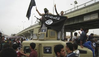 Islamic State group militants hold up their flag as they patrol in a commandeered Iraqi military vehicle in Fallujah, 40 miles (65 kilometers) west of Baghdad, on March 30, 2014. (Associated Press) **FILE**