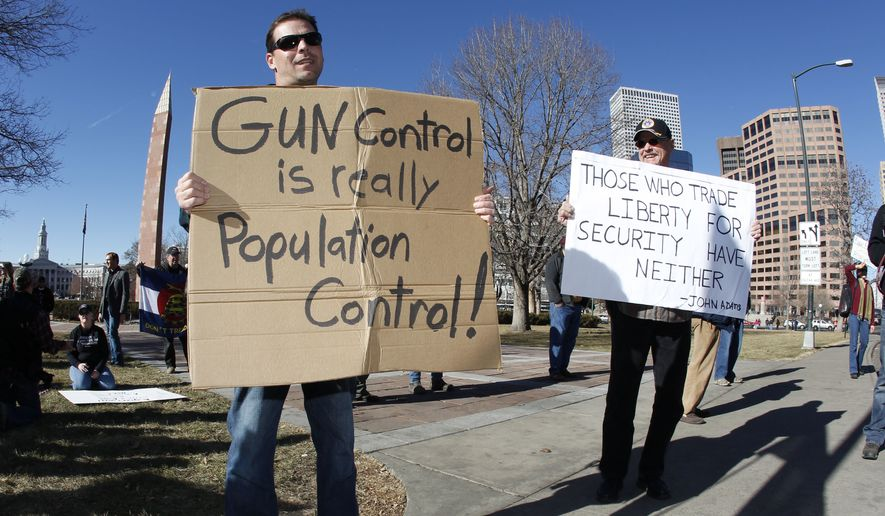 Craig Larson (right) of Fort Collins, Colo., and another protester who refused to identify himself wave signs during a pro-gun rally in a park across from the State Capitol in Denver on Jan. 9, 2013. (Associated Press) **FILE**