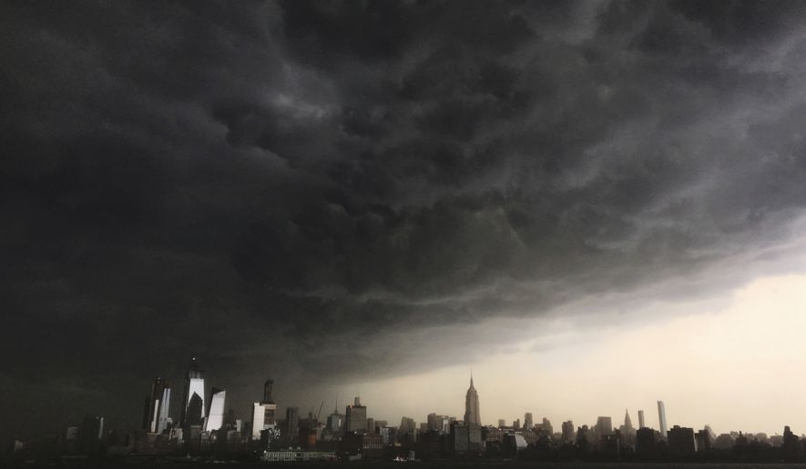 In this Tuesday, May 15, 2018 photo, storm clouds gather over New York city seen from the Hudson River. A line of strong storms pushed across New York City and badly disrupted the evening commute, stranding thousands of train riders. (AP Photo/Denis Paquin)