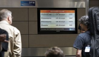 Passengers await their luggage after arriving at Dallas-Fort Worth International Airport from Philadelphia Thursday, Sept. 6, 2012, in Grapevine, Texas. A security  scare that prompted authorities to recall an airborne U.S. flight was the result of an apparent hoax, police said Thursday. (AP Photo/Tony Gutierrez)