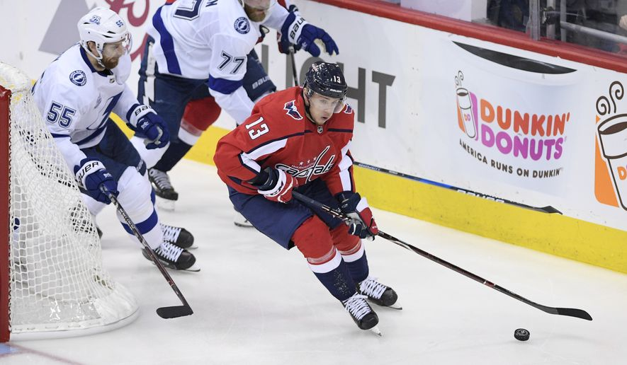 Washington Capitals left wing Jakub Vrana (13) skates with the puck against Tampa Bay Lightning defenseman Braydon Coburn (55) and defenseman Victor Hedman (77) during the third period of Game 3 of the NHL Eastern Conference finals hockey playoff series, Tuesday, May 15, 2018 in Washington. The Lightning won 4-2. (AP Photo/Nick Wass) ** FILE **