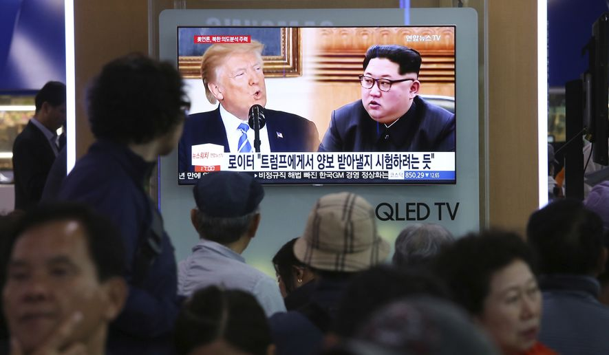 """People watch a TV screen showing file footage of U.S. President Donald Trump, left, and North Korean leader Kim Jong Un during a news program at the Seoul Railway Station in Seoul, South Korea, Wednesday, May 16, 2018. North Korea on Wednesday threatened to scrap a historic summit next month between its leader, Kim Jong-un, and U.S. President Donald Trump, saying it has no interest in a """"one-sided"""" affair meant to pressure Pyongyang to abandon its nuclear weapons. The signs read: """"Trying to test Trump."""" (AP Photo/Ahn Young-joon)"""