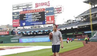 Washington Nationals relief pitcher Sean Doolittle walks off the field as the scoreboard at Nationals Park announces that both of today's interleague baseball games against the New York Yankees have been postponed due to inclement weather, Wednesday, May 16, 2018, in Washington. Both game have been rescheduled for June 18, 2018. (AP Photo/Pablo Martinez Monsivais)