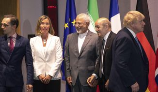 From left, German Foreign Minister Heiko Maa,  European Union foreign policy chief Federica Mogherini, Iranian Foreign Minister Javad Zarif, French Foreign Minister Jean-Yves Le Dria, and Britain's Foreign Minister Boris Johnson prepare to pose for a photo during a meeting of the foreign ministers from Britain, France and Germany with the Iran Foreign Minister and EU foreign policy chief Federica Mogherini, at the Europa building in Brussels, Tuesday, May 15, 2018. Major European powers sought Tuesday to keep Iran committed to a deal to prevent it from building a nuclear bomb despite deep misgivings about Tehran's Middle East politics and President Donald Trump's vehement opposition. (AP Photo/Olivier Matthys, Pool)