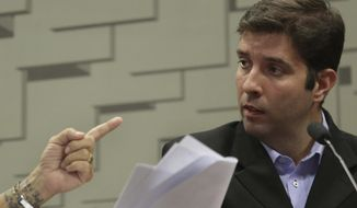 Brazil's former gymnastics coach Fernando de Carvalho Lopes, right, denies sexual abuse accusations, during his testimony to a Senate Committee, in Brasilia, Brazil, Wednesday, May 16, 2018. Lopes suggested that his accusers might have aligned their stories or been coached and said he wasn't sure why the athletes would do such a thing. (AP Photo/Eraldo Peres)