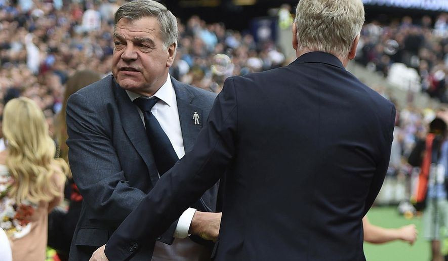 Everton manager Sam Allardyce, left, shakes hands with West Ham manager David Moyes, ahead of the English Premier League soccer match between West Ham United and Everton,  at the London Stadium, in London, Sunday May 13, 2018. (Daniel Hambury/PA via AP)