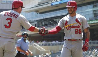St. Louis Cardinals' Tommy Pham, right, is congratulated by Jedd Gyorko after Pham scored on a two-run single by Dexter Fowler off Minnesota Twins pitcher Lance Lynn in the first inning of a baseball game Wednesday, May 16, 2018, in Minneapolis. (AP Photo/Jim Mone)