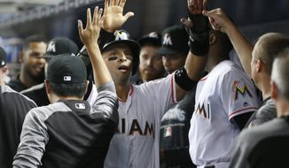 Miami Marlins' Martin Prado, center, is congratulated by teammates after scoring on a single by Brian Anderson during the first inning of a baseball game against the Los Angeles Dodgers, Wednesday, May 16, 2018, in Miami. (AP Photo/Wilfredo Lee)