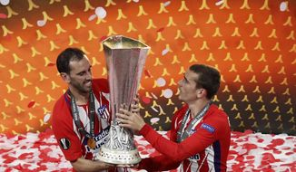 Atletico's Diego Godin, left, and Antoine Griezmann lift up the cup after the Europa League Final soccer match between Marseille and Atletico Madrid at the Stade de Lyon outside Lyon, France, Wednesday, May 16, 2018. Atletico Madrid won the Europa League for the third time with a resounding 3-0 victory. (AP Photo/Christophe Ena)