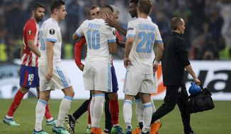 Teammates hugs Marseille's Dimitri Payet, center, as he walks off the pitch after sustaining an injury during the Europa League Final soccer match between Marseille and Atletico Madrid at the Stade de Lyon in Decines, outside Lyon, France, Wednesday, May 16, 2018. (AP Photo/Francois Mori)
