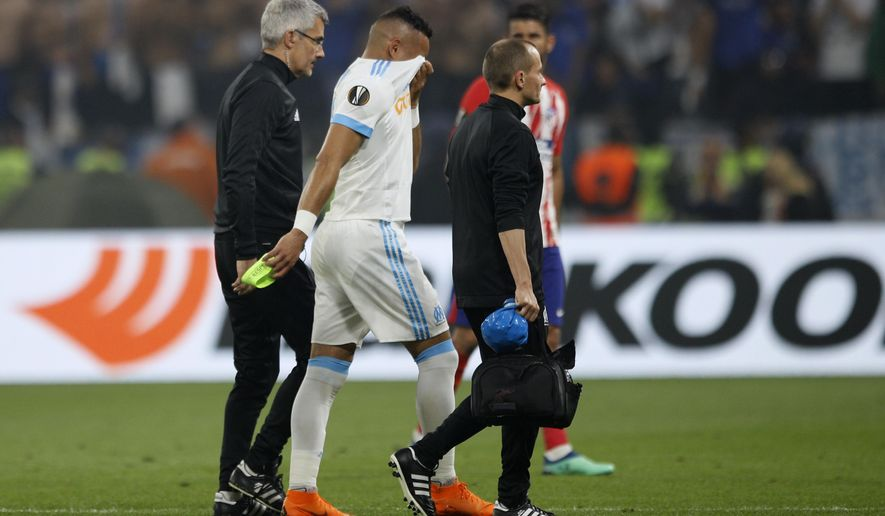 Marseille's Dimitri Payet walks off the pitch after sustaining an injury during the Europa League Final soccer match between Marseille and Atletico Madrid at the Stade de Lyon in Decines, outside Lyon, France, Wednesday, May 16, 2018. (AP Photo/Francois Mori)