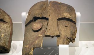 A historical wooden mask, plundered from the graves of indigenous Alaskans, is displayed during a ceremony at the Ethnological Museum in Berlin on Wednesday, May 16, 2018. The Ethnological Museum hand over the mask and other looted items from their collection to an official of the Chugach Alaska Corporation, which represents indigenous people in the Chugach region. (Ralf Hirschberger/dpa via AP)