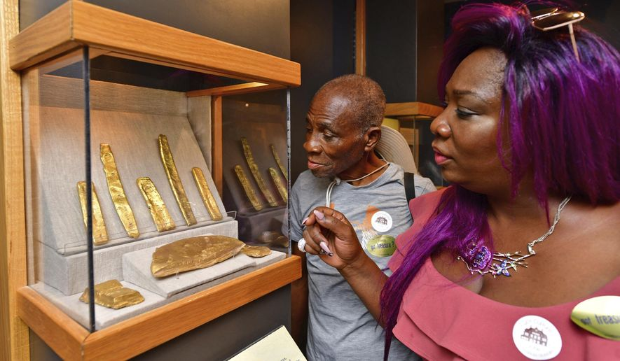 In this May 15, 2018 photo provided by the Florida Keys News Bureau, Jean-Lumarque Estime, left, and his daughter Linda Porsha Estime, examine gold artifacts from two Spanish shipwrecks while visiting the Mel Fisher Maritime Museum in Key West, Fla. On Wednesday, May 16, 2018, a Federal jury concluded that Jarred Alexander Goldman was guilty of conspiracy and theft of a gold bar similar to ones in the case. Another man, Richard Steven Johnson, has already pleaded guilty. The two men stole the bar from the museum in 2010 and are to be sentenced July 23. (Rob O'Neal/Florida Keys News Bureau via AP)