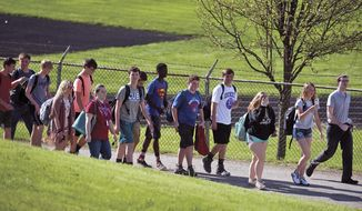 Students file into the adjacent National Guard armory following a shooting at Dixon High School Wednesday, May 16, 2018, in Dixon, Ill. A 19-year-old who showed up at his former high school in northern Illinois and opened fire on a police officer working there, was shot by the officer and taken into custody. The officer, who was not injured, was hailed a hero for his quick response protecting students and staff who had gathered at Dixon High School for a graduation rehearsal. (Alex T. Paschal/Sauk Valley Media via AP)