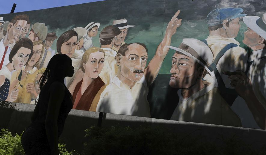 """In a Thursday, May 19, 2016 photo, people gather by the controversial mural painted by artist Dave Powers in Elgin, Ill.  The Elgin Cultural Arts Commission rejected artist David Powers' request Monday, May 14, 2018, for the return of his piece, """"American Nocturne."""" The city put the mural into storage after learning in 2016 that the painting was based on a crowd photographed during a 1930 lynching in Marion, Indiana. (Antonio Perez/Chicago Tribune via AP)"""