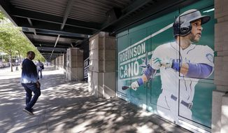 A man walks past an oversized photo of Seattle Mariners second baseman Robinson Cano outside the stadium before the team's baseball game against the Texas Rangers on Tuesday, May 15, 2018, in Seattle. Cano was suspended 80 games for violating baseball's joint drug agreement. (AP Photo/Elaine Thompson)