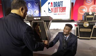 Arizona's DeAndre Ayton, right, shakes hands with the Rev, Jesse Jackson before the NBA basketball draft lottery Tuesday, May 15, 2018, in Chicago. (AP Photo/Charles Rex Arbogast)