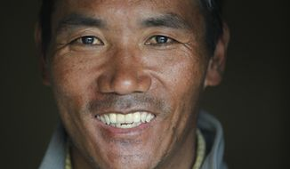 In this March 26, 2018 file photo, Nepalese veteran Sherpa guide, Kami Rita, 48, poses for a photograph at his rented apartment in Kathmandu, Nepal. Rita, scaled Mount Everest on Wednesday morning May 16 for the 22nd time, setting the record for most climbs of the world's highest mountain, officials said. (AP Photo/Niranjan Shrestha, File)