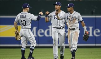 Tampa Bay Rays outfielders Johnny Field, Carlos Gomez and Mallex Smith, from left, fist-bump after the second baseball game of a doubleheader against the Baltimore Orioles, Saturday, May 12, 2018, in Baltimore. Tampa Bay won 10-3. (AP Photo/Patrick Semansky)