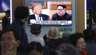 """People watch a TV screen showing file footage of U.S. President Donald Trump, left, and North Korean leader Kim Jong Un during a news program at the Seoul Railway Station in Seoul, South Korea, Wednesday, May 16, 2018. North Korea on Wednesday threatened to scrap a historic summit next month between its leader, Kim Jong Un, and U.S. President Donald Trump, saying it has no interest in a """"one-sided"""" affair meant to pressure Pyongyang to abandon its nuclear weapons. The signs read: """" Trying to test Trump."""" (AP Photo/Ahn Young-joon)"""