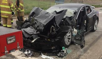 This Friday, May 11, 2018, file photo released by the South Jordan Police Department shows a traffic collision involving a Tesla Model S sedan with a Fire Department mechanic truck stopped at a red light in South Jordan, Utah. The driver of a Tesla electric car that hit a Utah fire department vehicle over the weekend says the car's semi-autonomous Autopilot mode was engaged at the time of the crash. (South Jordan Police Department via AP, File)
