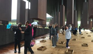 This April 26, 2018 photo shows visitors looking at markers bearing the names of lynching victims at the National Memorial for Peace and Justice in Montgomery, Ala. The memorial includes some 800 markers, one for each county in the U.S. where lynchings took place, documenting the killings of more than 4,400 individuals between 1877 and 1950. (AP Photo/Beth J. Harpaz)