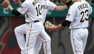 Pittsburgh Pirates' Adam Frazier, center, celebrates with Jordy Mercer (10), and David Freese (23) after the final out of a 3-2 win over the Chicago White Sox in a baseball game in Pittsburgh, Wednesday, May 16, 2018. (AP Photo/Gene J. Puskar)