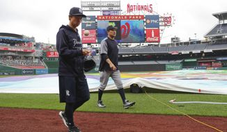New York Yankees starting pitcher Masahiro Tanaka, center, and his translator, Shingo Horie, left, walk off the field at Nationals Park after it was announced that both of today's interleague baseball games against the Washington Nationals have been postponed due to inclement weather, Wednesday, May 16, 2018, in Washington. Both game have been rescheduled for June 18, 2018. (AP Photo/Pablo Martinez Monsivais) ** FILE **