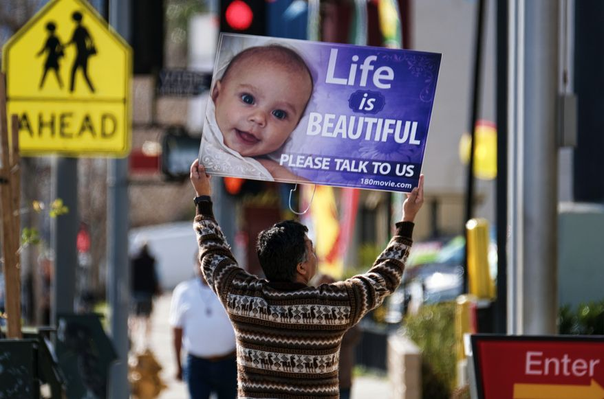 A protester carries a sign down the street near a Planned Parenthood health center in the Van Nuys section of Los Angeles on Saturday, Feb. 11, 2017. Several dozen protesters gathered in California's San Fernando Valley demanding the organization be stripped of its federal funding.  (AP Photo/Richard Vogel) ** FILE **