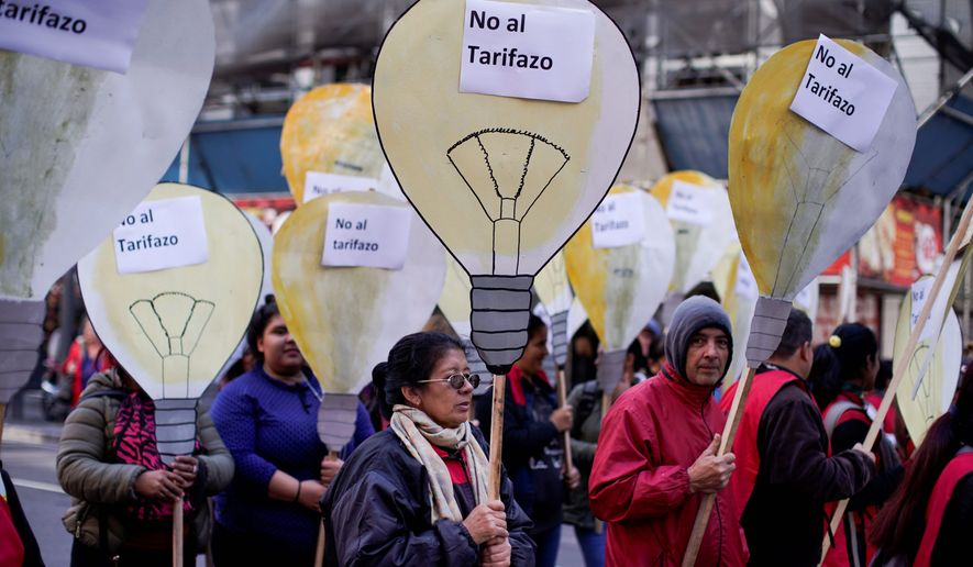 """People hold cutouts that look like light bulbs with signs that read in Spanish """"no to the price hike"""" during a protest against the economic policies of of Argentina's President Mauricio Macri in Buenos Aires, Argentina, Wednesday, May 16, 2018. Unions and opposition grassroots movements marched in downtown Buenos Aires against hike in tariffs, inflation, and a loan by the International Monetary Fund requested by the government after a currency crisis that weakened the peso in the past weeks. (AP Photo/Victor R. Caivano)"""