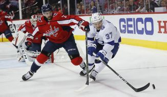 Washington Capitals defenseman Matt Niskanen (2) and Tampa Bay Lightning center Yanni Gourde (37) chase the puck during the first period of Game 4 of the NHL hockey Eastern Conference finals Thursday, May 17, 2018, in Washington. (AP Photo/Pablo Martinez Monsivais)