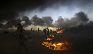 FILE - In this Tuesday, May 15, 2018 file photo, Palestinian protesters burn tires at the Gaza Strip's border with Israel, east of Khan Younis. The aftershocks of the U.S. Embassy move to Jerusalem and bloodshed on the Gaza border are shaking up the region, including the relationship between Palestinian President Mahmoud Abbas and former his negotiating partners, Israel and the U.S. Seething over a perceived U.S. betrayal on Jerusalem, Abbas is preparing to pursue what has been called his doomsday weapon, a war crimes complaint against Israel at the International Criminal Court. (AP Photo/Adel Hana, File)