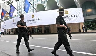 FILE - In this July 21, 2008, file photo, Singapore police officers patrol outside the Shangri-La hotel, a possible location for the upcoming Trump-Kim summit next month, in Singapore. Donald Trump and Kim Jong Un have one big thing in common as they prepare for what would be the first ever U.S.-North Korea summit: they both claim to deserve total credit. In a country where there is no Twitter but lots of fake news, North Koreans are getting a very different take on what got the two leaders to agree to meet next month in Singapore. (AP Photo/Dita Alangkara, File) **FILE**