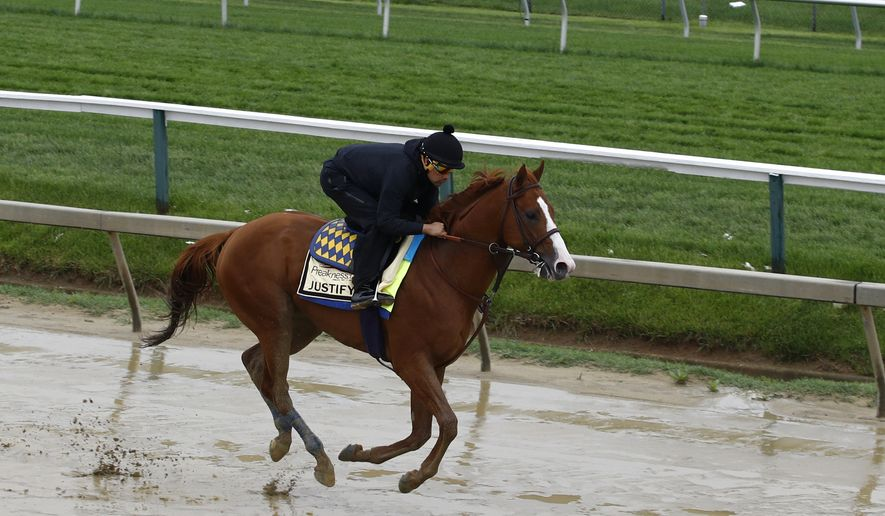 Kentucky Derby winner Justify, with exercise rider Humberto Gomez aboard, gallops around the track, Thursday, May 17, 2018, at Pimlico Race Course in Baltimore. The Preakness Stakes horse race is scheduled to take place Saturday, May 19. (AP Photo/Patrick Semansky)