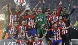 Atletico players with head coach Diego Simeone, far right in black, celebrate with the trophy after winning the Europa League Final soccer match between Marseille and Atletico Madrid at the Stade de Lyon in Decines, outside Lyon, France, Wednesday, May 16, 2018. (AP Photo/Francois Mori)