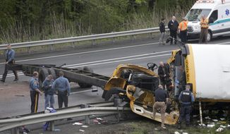 Emergency personnel examine a school bus after it collided with a dump truck, injuring multiple people, on Interstate 80 in Mount Olive, N.J., Thursday, May 17, 2018. (AP Photo/Seth Wenig)