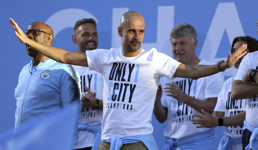 Manchester City soccer team manager Pep Guardiola acknowledges supporters during the British Premier League champions trophy parade in Manchester, England, Monday May 14, 2018.  Manchester City soccer team paraded through the streets of Manchester aboard open top buses, celebrating winning the Premier League title by a record 19 points. (Richard Sellers/PA via AP)