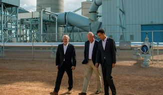 In this May 16, 2018 photo from left, Paul Kukut, CEO of Basin Electric Power Cooperative, Gov. Matt Mead and Marcius Extavour, senior director of the NRG COSIA Carbon XPrize walk across the Integrated Test Center grounds before the facility's dedication ceremony in Gillette, Wyo. (Rhianna Gelhart /Gillette News Record via AP)