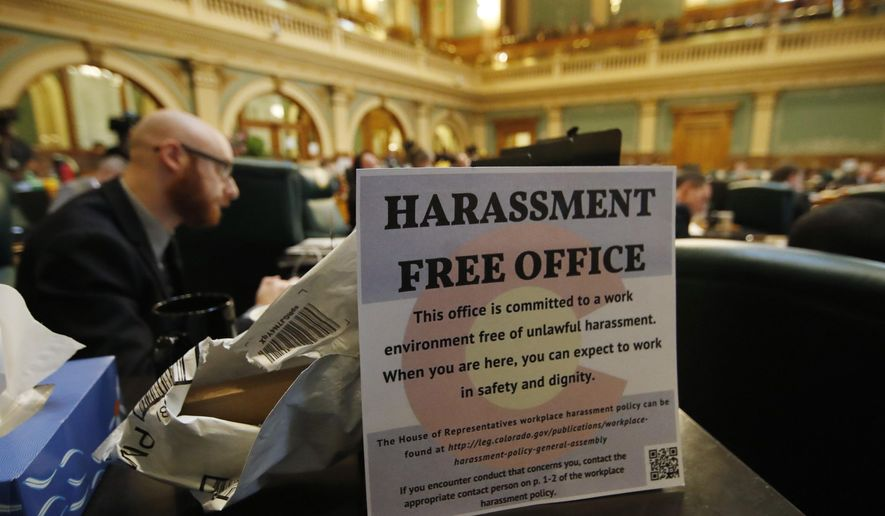 FILE - In this Friday, March 2, 2018, file photograph, a sign sits on the filing cabinet next to Colorado State Rep. Jonathan Singer, D-Longmont, during debate to expel State Rep. Steve Lebsock, D-Thornton, over sexual misconduct allegations from his peers in the State Capitol in Denver. Colorado lawmakers have deferred the passage of a new misconduct policy for lawmakers until the 2019 session comes to order next January. (AP Photo/David Zalubowski, File)