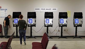 In this Oct. 19, 2017, file photo, Kelly Monroe, investigator with the Georgia secretary of state office, left, takes a look at a new voting machine being tested at a polling site in Conyers, Ga. (AP Photo/David Goldman, File)