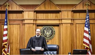 Assistant U.S. attorney Ryan Locker walks in during a mock trial at the Federal Courthouse in Tyler, Texas. Students from Bishop T.K. Gorman and All Saints participated in the mock trial as part of Law Day. (Chelsea Purgahn/Tyler Morning Telegraph via AP)
