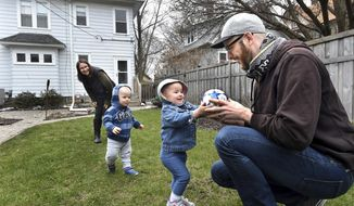 This photo taken April 8, 2016, shows Wes Burdine and Lydia Garver playing with their 17-month old twins, Emil, left, and Iris, in the backyard of their St. Paul, Minn. home. The couple purchased the house in March 2016. Burdine loves soccer, and the location of their four-bedroom home on Charles Avenue was based on three factors: finding an affordable neighborhood as first-time buyers, proximity to light-rail transit and being within walking distance of Minnesota United FC's soccer stadium being constructed nearby. (Jean Pieri /Pioneer Press via AP)