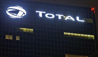 FILE - In this file photo taken on Oct.12, 2016, the logo of French oil giant Total SA is pictured at company headquarters in La Defense business district, outside Paris. French oil and gas company Total says it will not continue a multi-billion dollars project in Iran unless it is granted a waiver by U.S. authorities. (AP Photo/Michel Euler, File)