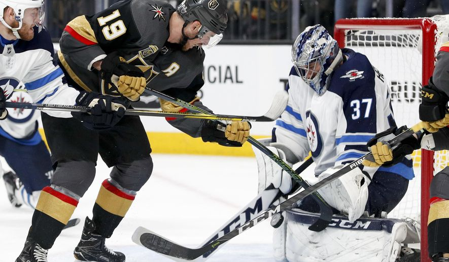 Winnipeg Jets goaltender Connor Hellebuyck, right, blocks a shot by Vegas Golden Knights right wing Reilly Smith during the second period of Game 3 of the NHL hockey playoffs Western Conference finals Wednesday, May 16, 2018, in Las Vegas. (AP Photo/John Locher)
