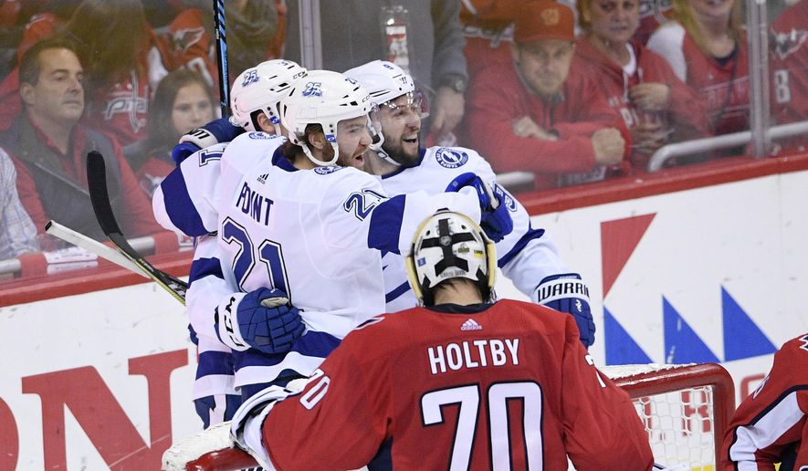 Tampa Bay Lightning center Brayden Point (21) celebrates his goal with center Tyler Johnson (9) next to Washington Capitals goaltender Braden Holtby (70) during the first period of Game 4 of the NHL hockey Eastern Conference finals Thursday, May 17, 2018, in Washington. (AP Photo/Nick Wass)
